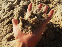 Hand holding sand on a beach. Having fun in the sand, hand holding sand on a beach Royalty Free Stock Photo