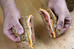 Hand holding sandwich. Hands holding turkey sandwich on counter top Royalty Free Stock Photos