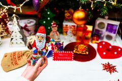 Free Hand Holding Santa Claus Chocolate Figurine In Front Of The Christmas Tree. Decorating Christmass Tree Isolated Stock Images - 195097014