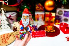Free Hand Holding Santa Claus Chocolate Figurine In Front Of The Christmas Tree. Decorating Christmass Tree Isolated Stock Photos - 195644383