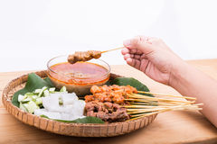 Hand holding satay served on traditional rattan plate with ingre Royalty Free Stock Images
