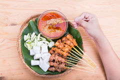 Hand holding satay served on traditional rattan plate with ingre Stock Images