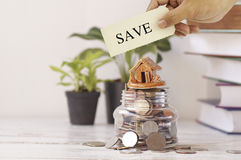 Hand holding save sign on home and coins Stock Photo
