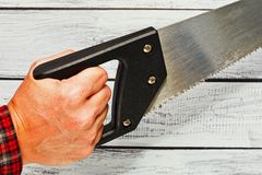 Hand holding a hand saw. Hand with rough skin of person wearing checkered work shirt holding a hand saw. Honest hand labor concept. Saw looks used. Close-up Stock Photo