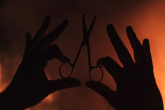 Hand Holding Scissors Against A Background Of Fire Dark Concept Stock Image