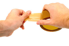 Hand holding scotch tape. Beige scotch tape in hand isolated on white Royalty Free Stock Image