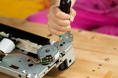 A hand holding a screwdriver is installing or repairing Royalty Free Stock Images