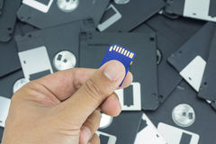 Hand holding SD card with floppy disk Stock Photography