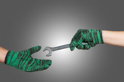 Hand holding and sending the wrench on gray background. industri Royalty Free Stock Image