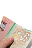 Hand holding a series of Canadian banknotes. With 100 dollars on top Royalty Free Stock Photo