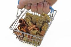 Plumber out shopping. A hand holding a shopping basket containing copper and brass fittings on an isolated white background Royalty Free Stock Image