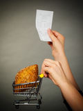 Hand holding shopping cart with bread and bill. Buying gluten food products concept. Woman hand holding shopping cart trolley with small piece of bread and Stock Photography