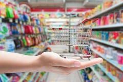 Hand holding shopping cart. With supermarket background Stock Image