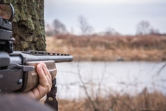 Hand holding shotgun aiming and ready to shot during hunting with copy space royalty free stock photo