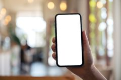 A hand holding and showing black mobile phone with blank white screen. Mockup image of a hand holding and showing black mobile phone with blank white screen in stock images
