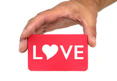 Hand holding and showing a red card with  LOVE  text and heart shape Royalty Free Stock Photos
