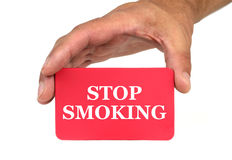 Hand holding and showing a red card with  STOP SMOKING  text Stock Photo