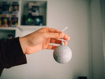 Hand holding a silver christmas ball stock photo
