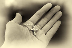 Hand holding a silver cross. Christianity royalty free stock photography