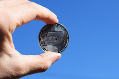 Hand holding silver Dash coin on blue sky background stock image