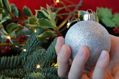 Hand holding a silver glitter Christmas ornament. Hand holding a glittery silver ornament with evergreen, lights, and holiday greenery in the background Royalty Free Stock Image