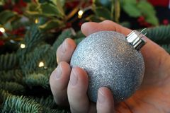 Hand holding a silver glitter Christmas ornament. Hand holding a glittery silver ornament with evergreen, lights, and holiday greenery in the background Stock Photography