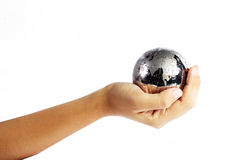 Hand holding silver globe. A close up view of a human hand and forearm holding a silvery globe or replica of the earth.  Isolated on white background Royalty Free Stock Photography