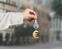 Hand holding silver key with golden euro sign shape keyring, 3D Royalty Free Stock Image