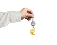 Hand holding silver key with golden euro sign shape keyring Royalty Free Stock Image