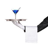 A hand holding a silver tray with a cocktail. A hand holding a silver tray with a blue cocktail on it isolated on white background royalty free stock image