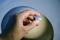Hand Holding SIM Module Over Silicon Wafers Royalty Free Stock Images