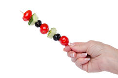 Hand holding a skewer with cherry tomatoes, cucumber and olives Royalty Free Stock Images