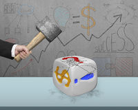 Hand holding sledgehammer hitting white dice with doodles wall Royalty Free Stock Photo