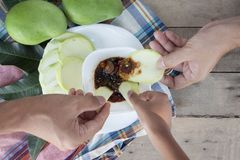Hand holding Sliced Mangoes with sweet fish sauce. stock photos