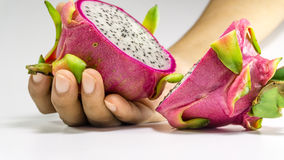 Hand holding a slices of Dragon fruits. Hand holding a slices of bright juicy tropical dragon fruit royalty free stock photography