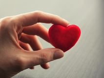Hand holding small bright red heart Royalty Free Stock Photos