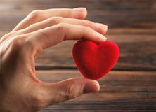 Hand holding small bright red heart Royalty Free Stock Photo