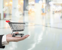 Hand holding small 3D empty shopping cart Stock Image