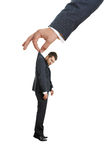 Hand holding small discontented man. Big hand holding small discontented businessman. isolated on white background royalty free stock images