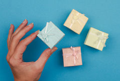 Hand holding a small gift box on blue background Stock Photos