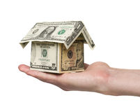 Hand holding a small house built out of dollar bil Stock Photography