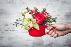 Hand holding Small red vase with bouquet of flowers on gray space for text Royalty Free Stock Image