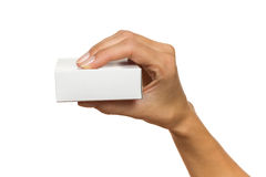 Hand Holding Small White Box. Close up of woman's hand holding white carton box. Studio shot isolated on white Royalty Free Stock Image
