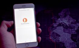 Hand holding smarphone with DuckDuckGo search engine displayed. Hand holding smartphone with a DuckDuckGo search engine displayed. Dark map in a background royalty free stock photos
