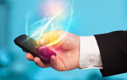 Hand holding smart phone with abstract glowing lines Royalty Free Stock Image