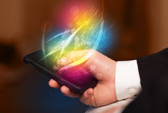 Hand holding smart phone with abstract glowing lines Stock Photography