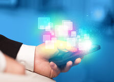 Hand holding smart phone with abstract glowing squares Stock Photos