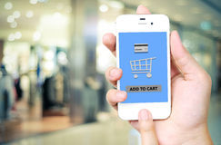 Hand holding smart phone with add to cart words on screen over b Stock Photo