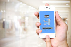Hand holding smart phone with add to cart words on screen over b Stock Images
