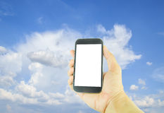 Hand holding smart phone on blue sky and cloud background Stock Photography
